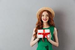 Ung kvinna för gladlynt rödhårig man i hållande gåva för grön klänning arkivbild