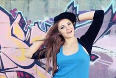 Ung kvinna för gladlynt tonåring mot väggen Arkivfoton