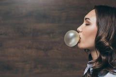 Ung kvinna för härlig brunett som blåser bubbelgum Arkivfoto
