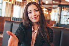 Ung kvinna för härlig charmig flicka för brunett som lycklig asiatisk ger handskakningen, hand av hjälp som hälsar på kafét arkivbilder