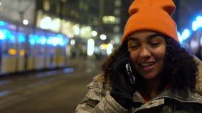 Ung kvinna för härlig kvinnlig tonåringflicka för blandat lopp som talar på natten på mobiltelefonen på natten med spårvagnar vid stock video
