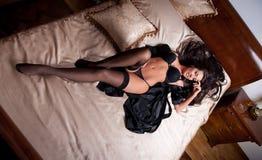 Ung kvinna för härlig och sexig brunett som bär svart damunderkläder i säng. Modeforsdamunderkläder inomhus. Sexig ung flicka i sv Arkivbild
