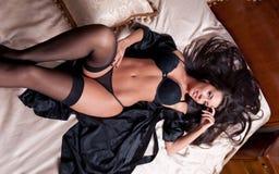 Ung kvinna för härlig och sexig brunett som bär svart damunderkläder i säng. Modeforsdamunderkläder inomhus. Sexig ung flicka i sv Royaltyfria Bilder
