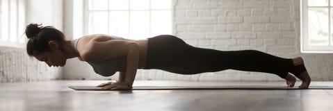 Ung kvinna för horisontalbild som gör -lemmad personalövning för yoga fyra royaltyfri fotografi