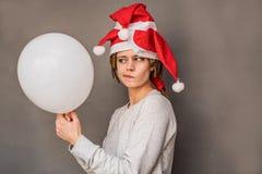 Ung kvinna för jul som rymmer en ballong som håller ögonen på med tvivel Royaltyfri Bild
