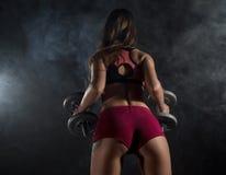 Ung kvinna för kondition i utbildning med hantlar, sportig muskulös kvinnlig brunett i rök arkivbild