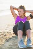 Ung kvinna för kondition som gör buk- knastrande på stranden Arkivfoto
