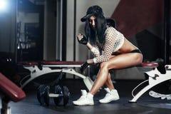Ung kvinna för kondition som vilar efter övning med hantlar i idrottshallen fotografering för bildbyråer