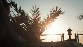 Ung kvinna för kontur som dricker coctailen på stranden på solnedgången på bakgrund arkivfilmer