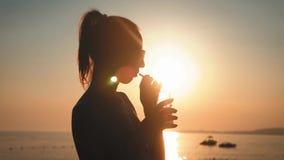 Ung kvinna för kontur som dricker coctailen på stranden på solnedgången på bakgrund stock video