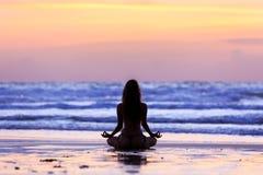 Ung kvinna för kontur som gör yoga på stranden på solnedgången royaltyfria foton