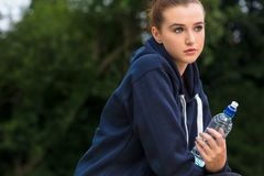 Ung kvinna för ledsen tonåring som dricker flaskan av vatten Royaltyfri Bild