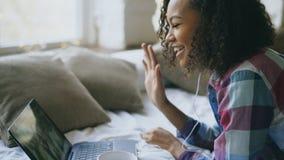 Ung kvinna för lockig afrikansk amerikan som har video pratstund med vänner som använder bärbar datorkameran, medan ligga på säng royaltyfri foto