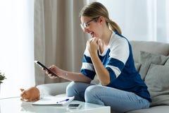 Ung kvinna för lycka som använder räknemaskinen och räknar hennes besparingar, medan sitta på soffan hemma royaltyfria foton