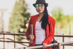 Ung kvinna för lycklig hipster som arbetar på bärbar datoroutdors Studentflicka som använder bärbara datorn i universitetsområde  Arkivfoto