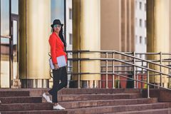 Ung kvinna för lycklig hipster som arbetar på bärbar datoroutdors Studentflicka som använder bärbara datorn i universitetsområde  Royaltyfria Bilder