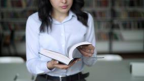 Ung kvinna för mellersta skott som bläddrar en encyklopedi på bakgrund av arkivhyllor lager videofilmer