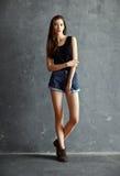 Ung kvinna för mode på grungeväggbakgrund Royaltyfri Foto