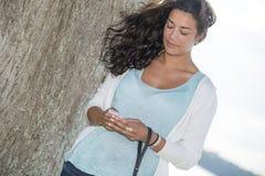 Ung kvinna för modemodell som utomhus kontrollerar korta meddelanden Royaltyfria Bilder
