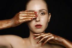 Ung kvinna för modeskönhet med guld- händer royaltyfri bild
