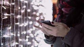 Ung kvinna för närbildhänder som använder smartphonen i den fallande snön på julnatten som står den near ljusväggen, stock video
