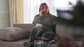 Ung kvinna för Plys format som ler, medan tala på den smarta telefonen som sitter inomhus onderfilten på soffan Plus formatkvinnl lager videofilmer