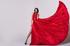 Ung kvinna för skönhet, i att fladdra den röda klänningen arkivfoton