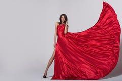 Ung kvinna för skönhet, i att fladdra den röda klänningen royaltyfri foto