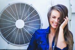 Ung kvinna för skönhet med att betinga för luft nära lyckligt skratta för fan hår long Trendig dam med en härlig frisyr, makeup Royaltyfria Bilder