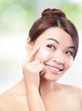 Ung kvinna för skönhet som applicerar skönhetsmedelkräm Fotografering för Bildbyråer
