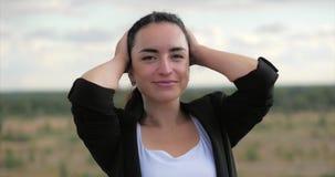 Ung kvinna för stående som ser i kameran på solnedgången, lyckad flicka som tänker om liv på naturen, tycka om arkivfilmer