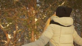 Ung kvinna för vinter som ser upp på kopieringsutrymmeyttersidan på snöig kall dag i skog lager videofilmer