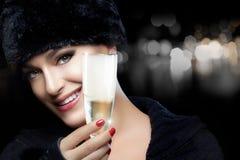 Ung kvinna för vintermode i pälshatt som rostar med Champagne Arkivbild