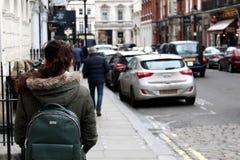Ung kvinna/flicka som undersöker London med en grön ryggsäck Royaltyfri Bild