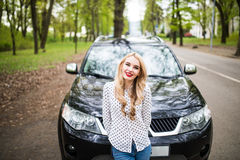 Ung kvinna framme av hennes bil på stadsgatan royaltyfri foto