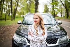 Ung kvinna framme av hennes bil på stadsgatan arkivfoto