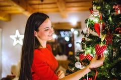 Ung kvinna framme av julgranen som dekorerar det royaltyfri foto