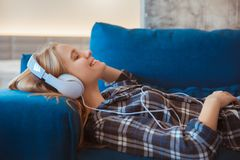 Ung kvinna hemma i le för musik för vardagsrum lyssnande royaltyfria bilder