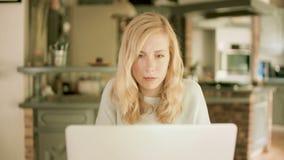Ung kvinna hemma som skriver på hennes bärbar dator lager videofilmer