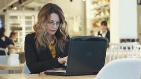 Ung kvinna i affärsdräkten som arbetar på bärbar datorsammanträde i kafé Informell arbetsmiljö arkivfilmer