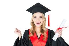 Ung kvinna i akademisk kappa och hållande diplom för akademikermössa på vit Royaltyfria Foton