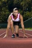 Ung kvinna, i att sprinta pos. royaltyfri foto
