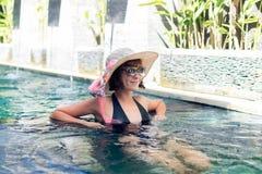 Ung kvinna i baddräkt i simbassäng i den ursnygga semesterorten, lyxig villa, tropisk Bali ö, Indonesien Royaltyfria Foton