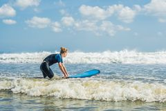 Ung kvinna i baddräkt med bränning för nybörjare som är klara att surfa P royaltyfri bild