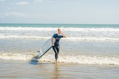 Ung kvinna i baddräkt med bränning för nybörjare som är klara att surfa P fotografering för bildbyråer
