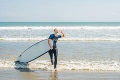 Ung kvinna i baddräkt med bränning för nybörjare som är klara att surfa P royaltyfri foto