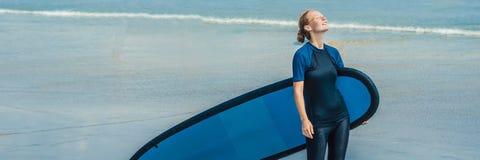 Ung kvinna i baddräkt med bränning för nybörjare som är klara att surfa Positivt sinnesrörelseBANER, LÅNGT FORMAT arkivbild