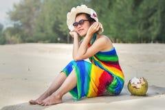 Ung kvinna i baddräkt med kokosnötcoctailen Fotografering för Bildbyråer