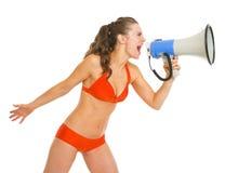 Ung kvinna i baddräkt som ropar till och med megafonen Arkivfoton
