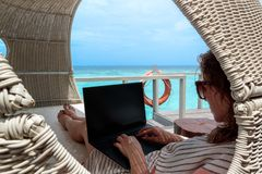 Ung kvinna i baddräktarbete på en dator under ferie Klart bl?tt tropiskt vatten som bakgrund arkivfoto